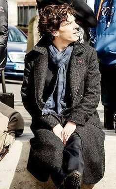 Ben With Dark Brown Hair As Sherlock Sitting on the Ground Wearing Black Overcoat and Blue and Gray Striped Scarf