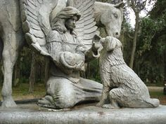 A statue of an angel with a dog, a cat, and a horse is located in the Garden of Love Pet Memorial Park in Micanopy, Florida, USA.