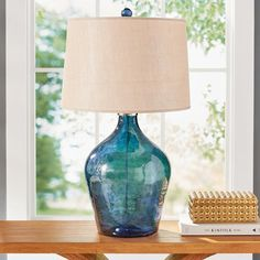 This is an alpha lamp, because the richly colored Lamone Table Lamp is big, bold, and gorgeously crafted. It's not going to get swamped by everything else in the room. The lightly hammered blue glass has a unique updated texture against the polished, nickel-plated details. When you have a clean modern space, or tend to style your home with jewel-toned room accents like pillows, art, or rugs, this is the lamp that pulls it all together for you, while maintaining its o...