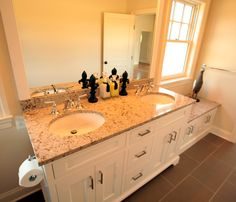 Inset doors and drawers on this his and hers vanity sink cabinet, flanked to one side by a matching bench seat, creates a warm and relaxing atmosphere that would be welcome in any master or guest bathroom.  #stone #double #sink #bench #bathroom #remodel #framed #mirror #vanity #base #painted