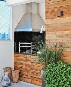 Um cantinho de sacada com churrasqueira muito charmosa decorada com painéis em madeira de demolição