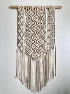 This chunky macramé wall hanging would make a stylish addition to any modern home. The intricate knotting forms a diamond effect and Ive used a pine dowel to hang it from. The unbleached cotton has a nice creamy colour to it. The overall size is 40 cms wide by 66 cms long (16 x