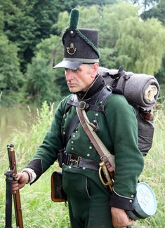 Uniform of the 95th Rifles (according to the re-enactors of the 2nd Battalion 95th). Notice the square-cut peak and the green braid round the base of the shako; also the small copper priming flask on a cord round the neck, and stowed in a pocket under the left arm. There is a matching pocket on the other side.
