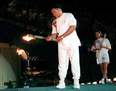 Ali lights the Olympic flame as American swimmer Janet Evans looks on during the 1996 Summer Olympic Games opening ceremony in Atlanta, July 19, 1996.
