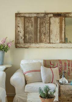 Buckets of Burlap blog. Our den in Prairie Style Magazine. Vintage door, grain sacks, pillows, white sofa, burlap, flowers, sap bucket, seltzer bottle, styled by Fifi ONeill, Mark Lohman photography