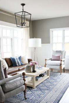 Grey love seat and white chairs on blue area rug