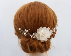 The pure silk bridal headpiece with freshwater pearls and Swarovksi crystals is handmade with pure silk organza. Flower petals are cut by hand, hand pressed by hand and assembled one by one with millinery methods. The center of each bridal hair flower is beaded with a large cluster of freshwater pearls and Swarovski crystals. The headpiece is finished with a beaded crystal leaf accents. The focal pure silk organza flower pictured in ivory measures approx. 2.75-3 in diameter. The floral…