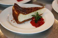 Amerikanischer Cheesecake mit Zucker bestreut, caramelisiert und eine kleine Note aus Waldfrüchten dazu, gespickt mit Minze