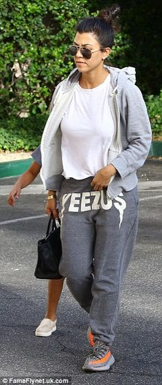 At ease: Kourtney was laid-back in a white T-shirt, which she layered under a grey tracksuit
