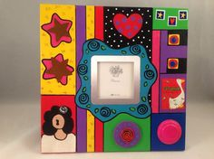 """Hand Painted 3""""x3"""" Photo Frame with 3D Attachments  Acrylic paint with polycrylic finish  Frame dimensions 9""""x9"""" excluding attachment  Holds one 3""""x3"""" photo  An original, one of a kind piece   $50.00"""