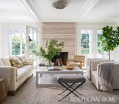 A striéd wood coffee table sets the tone in the living room, which features a long linen-blend sofa facing two Ultrasuede armchairs that swivel so family or guests can also watch a TV on an adjacent wall. - Photo: John Bessler / Design: Cynthia Hayes