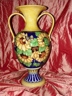 Vaso con due manici con girasole e farfalle su fondo blu -su piede motivo geometrico-