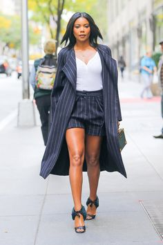 Gabrielle Union wears a pinstripe short power suit, a micro-trunk from Louis Vuitton, and open-toe heels