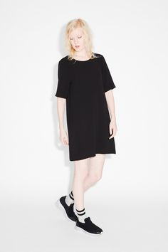 A light and textured shift dress with a wide round collar and long tee sleeves, this piece is all things cool, easy n' elegant. colour: black magic  In a size…