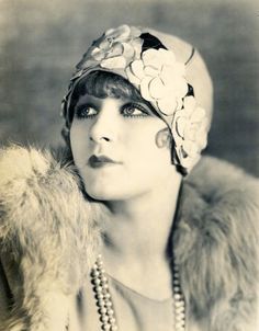Women wore different, colorful hats in the 20's. This woman is wearing very bright clothing and has her hair cut short. This was the style in 1920 because women were being less modest. Shorter hemlines and bright colors were very big in this era.