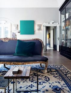 French settee and modern art in a living room with a streamlined coffee table.