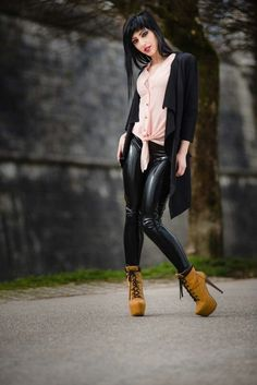 Black PVC pants worn by model who is also wearing a baby pink tie-front blouse…