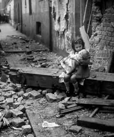 A young girl holds her doll while sitting on a busted beam in a debris ridden street the morning after a Luftwaffe bombing, 1940.