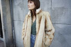 """""""As kids, our parents dressed us in hand-me-downs, and now we see how special it is to wear something no one else has,"""" says Miranda of the faux fur jacket she scored at a thrift store in Berlin. Elektra wears a trench coat from Swedish fast-fashion brand H&M's eco-conscious collection with vintage Levi's 501 jeans."""