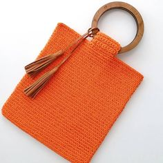 crocheted bag in vibrant orange with wooden handles and leather tassels :)