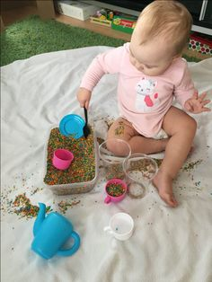 9. Sensory rice play    There are many ways  to play with colored rice. At 14 months Scarlett's favorites are: hiding small toys in rice, walking on rice, transferring rice to small containers, making rice rain, and pouring rice through a funnel. There are more ideas at 12 colored rice play ideas.