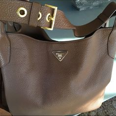 Prada Daino Wide Strap Hobo Bag Beautiful rich brown, pebbled Calf leather hobo bag with gold hardware. Wide, flat, adjustable shoulder strap. Signature triangle logo top center. Perfect condition used only a few times. Center snap closure at top. Interior pocket. Made in Italy. Purchased at Neiman Marcus- authentic!!! Prada Bags Hobos
