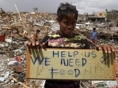 A typhoon victim holds a placard asking for food in the aftermath of super typhoon Haiyan in Tanauan - ask the Lord to show him how much He loves him...pray and give what you can...