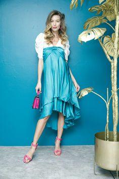 Camisa blanca con mangas abombadas MAP, falda azul turquesa con moño, sandalias con textura de víbora rosa Westies, bolsa metálica rosa Cloe y arracadas de corazones That´s It.