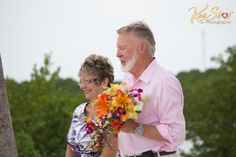 The father of the groom is holding the bouquet during the romantic wedding ceremony on Sombrero beach, Marathon Florida.