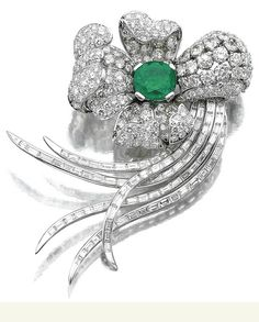 EMERALD AND DIAMOND CLIP Of stylised floral design, the pistil set with an oval emerald, the petals with circular- and brilliant-cut diamonds, to the baguette diamond stem, mounted in platinum.