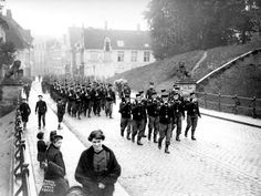 Belgian soldiers march through the Menin Gate (Meensepoort) at Ypres on 28 May 1914, just months before the German invasion of Belgium in August 1914. The old medieval 'gate' was by this time merely a gap in the 17th century defensive ramparts of the town from which the road ran to the town.
