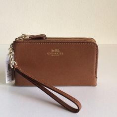 Coach Double Corner Zip Saddle Brown Wristlet Leather Inside multifunction pocket Zip closure, fabric lining Wrist strap attached 6 1/4 (L) x 4 (H) Coach Bags Clutches & Wristlets
