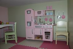 Toy-room under the stairs. Kid Kraft Retro Wooden Kitchen, Kid Kraft country table and chairs set with 2 foot square interlocking foam blocks all purchased on Amazon. I bought 3M's removable picture hangers to hang her pots and pans on the wall.