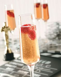 Ice cubes 1 ounce raspberry liqueur 1/2 ounce orange liqueur 1/2 ounce pomegranate juice 3 fresh raspberries 1/2 cup chilled Champagne