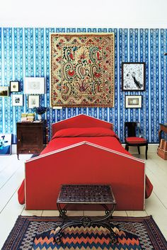 Vibrant living space with red bed and blue wallpaper