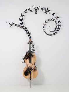 Paul Villinski's butterflies made out of recycled beer cans that once littered the streets of New York flutter out of a cello.