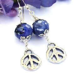 Inspired by the John Lennon song of the same name, the GIVE PEACE A CHANCE handmade earrings make a peace filled statement any time you wear them. Created with artisan made, rustic sterling silver peace signs, they also featured faceted blue sodalite gemstones, lead free pewter leaf bead caps and sterling silver earwires. One of a kind fashion jewelry for the free spirited, socially conscious woman, the GIVE PEACE A CHANCE dangle earrings were carefully designed and handmade by Catherine…