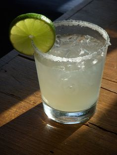 Fresh lime wedge   Margarita salt   Ice  1/3 cup fresh lime juice  3 tablespoons orange liqueur  2 tablespoons tequila  1/3 to 1/2 cup powdered sugar  Garnish: lime slice