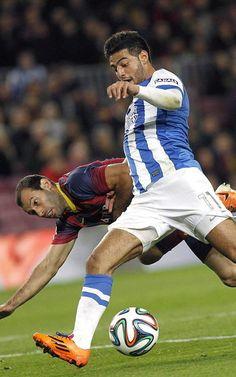 El mexicano Carlos Vela, de la Real Sociedad, controla el balón junto al argentino Javier Mascherano