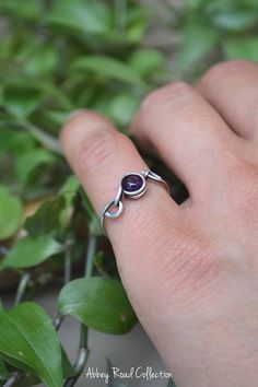 Amethyst Silver Wire Wrapped Ring This wire wrapped ring features a deep purple Amethyst stone in a unique silver wire design. The ends of the ring band curl up creating an elegant fantasy design and in the center, the gemstone is separately attached allowing for gentle movement #wirewrappedringsband