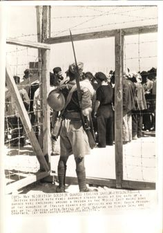 Photo dated May 16, 1941 showing a British soldier guarding captured Italian sailors
