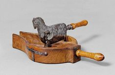 AN ORNATE FRUITWOOD AND WROUGHT IRON CHOCOLATE CUTTER, France, 19th c. The blade in the shape of a horse. L ca. 33 cm.