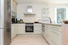 Omfangsrik kjøkkeninnredning med integrerte hvitevarer og benkeplate i stein og heltre eik | Drømmekjøkkenet