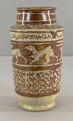 Albarello Date: late 12th–early 13th century Geography: Iran; Kashan Medium: Stonepaste; luster-painted on opaque white glaze Dimensions: H. 7 1/4 in. (18.4 cm) Max. Diam. 4 in. (10.2 cm)