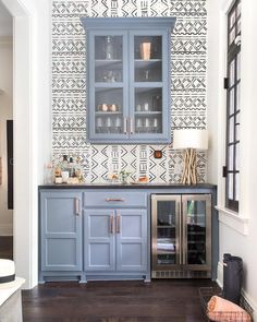 A dual glass door beverage fridge is fitted to blue paneled cabinets accented with copper hardware and a black countertop.
