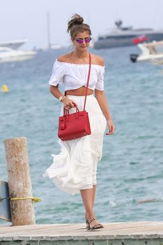 Taylor Hill wearing an off-the-shoulder white crop top, cream colored midi skirt, red cross-body bag, sandals, and purple sunglasses