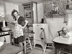 Boiling diapers with baby on table in 1943.