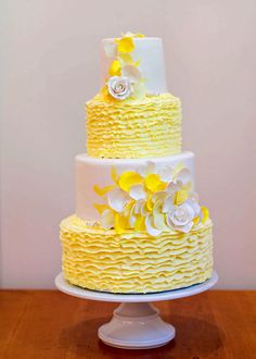 This cake is inspired by the brightness and warmth of summer when all things are in bloom. This design is suited for an outdoor garden or beach reception. The cake includes an arrangement of fondant and buttercream textures in yellow, white and a hint of gold with hand made roses and petals.