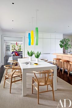 Vistosi pendant lights purchased at auction at Phillips de Pury complement a bespoke table in the kitchen; the Hans J. Wegner chairs are from Furniture from Scandinavia, and the rug is by Stark.