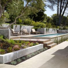 backyard concrete above ground lap pool built onto gentle slope